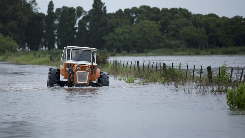 A man drives a tractor though a flooded road near Carmen de Areco, Argentina, Monday, Nov. 3, 2014.  Heavy rain since Thursday has killed two people in the province of Buenos Aires and thousands have evacuated the area. (AP Photo/Natacha Pisarenko)